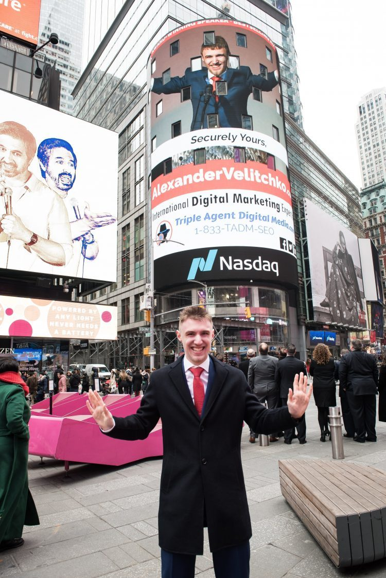 Alexander Velitchko standing in front of his likeness being displayed on the 75 foot tall Nasdaq Jumbotron in Times Square, New York City, with observers looking at the Nasdaq Jumbotron in the mid-ground